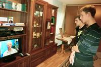 Посетители музея смотрят телепередачу Гордость России, посвященную Зое Куприяновой