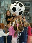 Юные посетителю у витрины, посвященной футболу