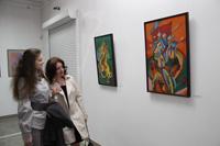 Посетители выставки «На берегах иных миров» перед картинами Татьяны Туркулец